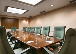 boardroom style layout in one of our meeting rooms with long green chairs